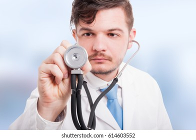 Close-up of young male doctor listening with stethoscope as cardiology concept