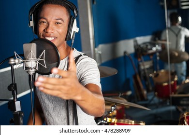 Closeup of a young male singer recording a track in a studio