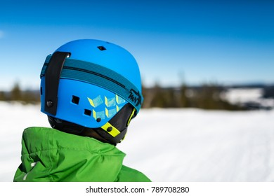 Close-up of young male skier standing on ski piste at ski resort on sunny winter day.