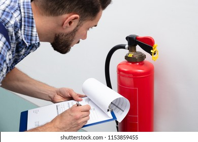 Close-up Of A Young Male Technician Checking Fire Extinguisher Writing On Document