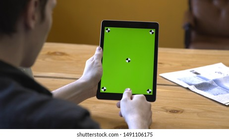 Close-up of young man in black shirt sitting at the wooden table with tablet and sliding on the chroma key green screen. Stock footage. Chroma key on the screen of the tablet in the hands.