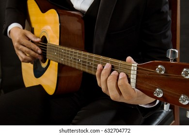 Close-up a young man in a black suit playing guitar isolated on black backgroud.