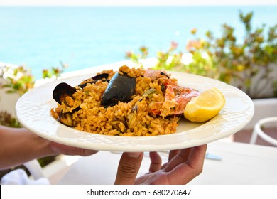 closeup of a young man bringing a plate of typical spanish paella, with seafood, to a table set for lunch, with the sea in the background