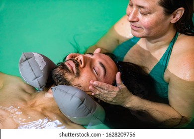 Close-up of young man with closed eyes wearing rubber neck pillow. around his neck getting spa water massage treatment from trainer in swimming pool