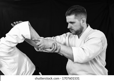 Close-up of a young man doing a painful hand technique from aikido technique