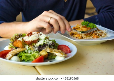 Closeup of young man eating spaghetti and salad in the cafe
