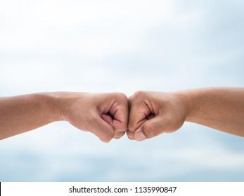 Closeup young man fist bump on the blue sky sea background. Friendship & Teamwork Concept.