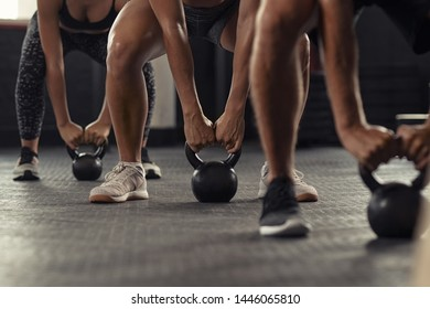 Closeup of young man and fit woman hands lifting kettle bell while squatting at gym. Athlete people doing weight lifting with kettlebell. Group of three young athlete doing crossfit training.