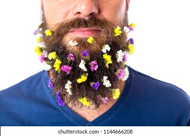 Close-up of young man with flowers in his beard standing against white background