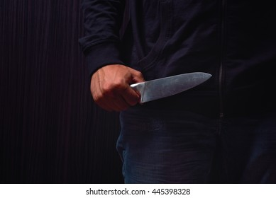 Closeup of a young man hand, holding a knife, about to attack, over black background. Representing the concept of danger, stress, unfulfillment, risk. Lights and shadows