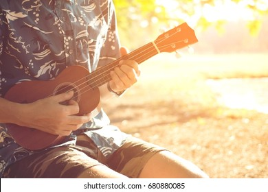 Closeup of young man hands playing acoustic guitar ukulele at the park sit Enjoy living Sunshine in the evening.