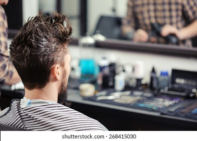 Close-up of a young man with his hair raised upwards sitting before the mirror at barbershop