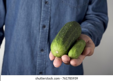 closeup of a young man holding a big cucumber next to a smaller one in his hand