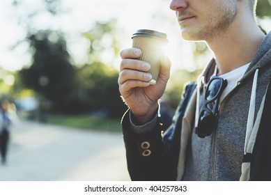 Close-up of young man holding coffee to take away at early morning in sunny park, sunlight, blurred background