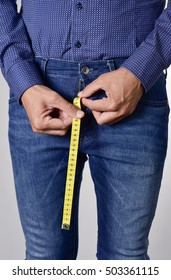 closeup of a young man holding a long piece of measuring tape that is popping up from the fly of his jeans
