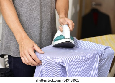 closeup of a young man ironing a striped shirt with an electric iron