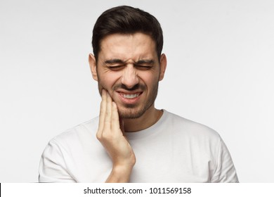 Closeup of young man isolated on gray background touching his face and closing eyes with expression of horrible suffer from health problem and aching tooth, showing dissatisfaction