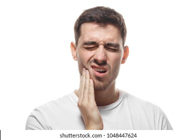 Closeup of young man isolated on white background touching his face and closing eyes with expression of horrible suffer from health problem and aching tooth