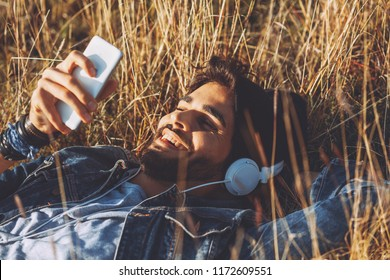 Closeup of young man listens to music via headhpones and smartpohone