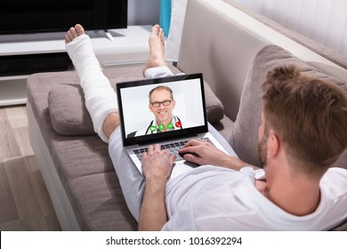 Close-up Of A Young Man Lying On Sofa Video Conferencing With Doctor On Laptop