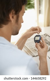 Closeup of young man measuring sugar with blood glucose meter at home