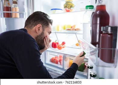 Close-up Of A Young Man Noticing Smell Coming From Foul Food In Refrigerator