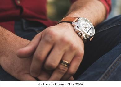 Closeup of young man outdoors in casual clothing wearing fancy wristwatch