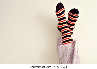 closeup of a young man in pajamas with his feet against the wall