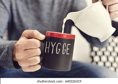closeup of a young man pouring milk into a mug with coffee or tea, where there is the the text hygge, a danish and norwegian word for comfort or enjoy, which can be a whole philosophy of life