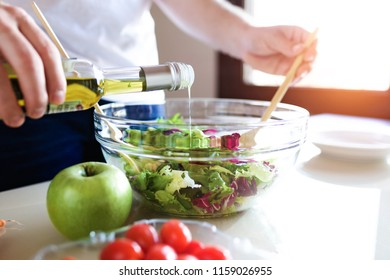 Close-up of young man preparing salad in the kitchen.