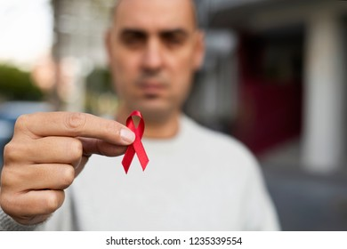closeup of a young man with a red awareness ribbon for the fight against AIDS in his hand