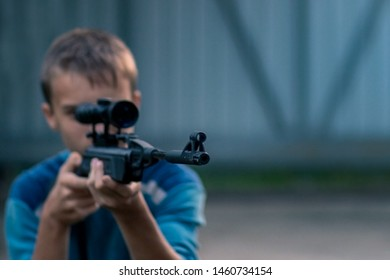Close-up of young man shooting. Teenager boy training with sniper air rifle.