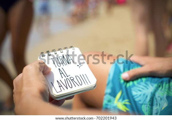 closeup of a young man sitting in a deck chair in the seashore of a beach showing a spiral notepad with the text torna al lavoro, back to work in Italian, handwritten in it