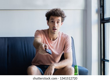 close-up of young man sitting on a sofa and changing channel with a remote control