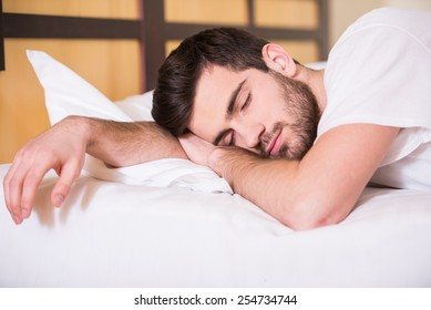 Close-up of young man is sleeping on bed.