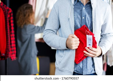 Closeup of young man is stealing red jeans in store, shop, boutique at shopping center. Guy is hiding unpaid good under clothes. Seller, assistant caught thief on hot. Shoplifting concept.