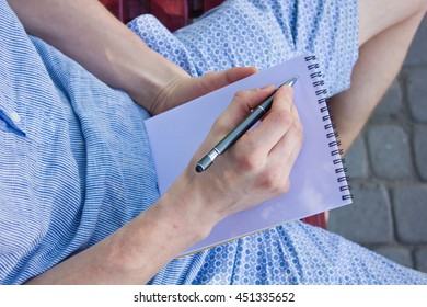 Closeup of young man taking notes at the notebook