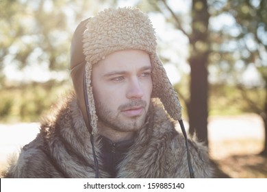 Close-up of a young man in warm clothing looking away in forest on a winter day
