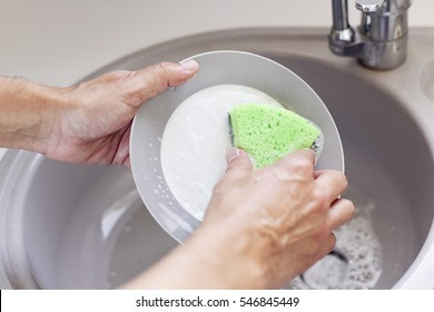 closeup of a young man washing dishes in a kitchen sink with a green sponge