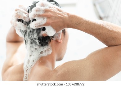 Closeup young man washing hair with with shampoo in the bathroom, health care concept, selective focus