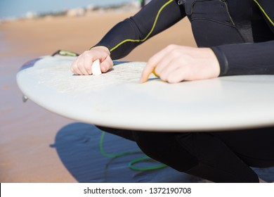 Closeup of young man waxing surfboard on sunny beach. Guy wearing wetsuit, crouching and holding surf board. Surfboarding concept. Cropped view.
