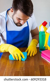 Closeup Of Young Man Wearing Apron Cleaning Kitchen Worktop, set cleaning concept