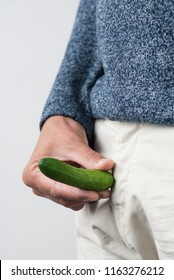 closeup of a young man wearing beige pants holding a small cucumber in front of his crotch