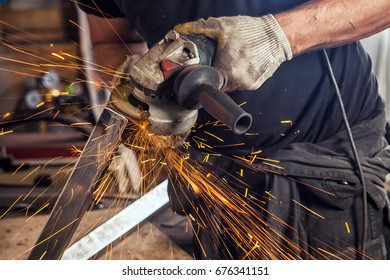 Close-up A young man welder wearing a black T-shirt is grinds metal with an angle grinder in the workshop, in the background a lot of tools are flying towards the side sparks