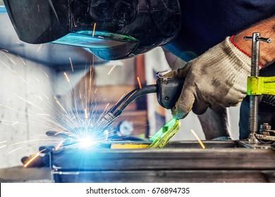 Close-up A young man welder wearing a black welding mask   weld a metal welding machine in a garage