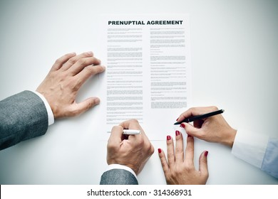closeup of a young man an a young woman signing a prenuptial agreement