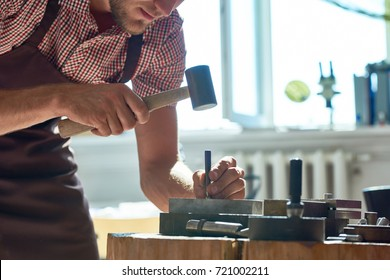 Closeup  of young man working with metal  in workshop, forming it with mallet on work station with different tools