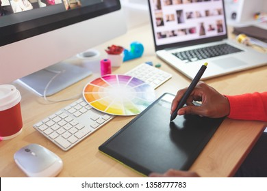 Close-up of young mixed-race female graphic designer using graphic tablet at desk in a modern office