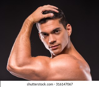 Close-up of young muscular man is looking at the camera on black background.