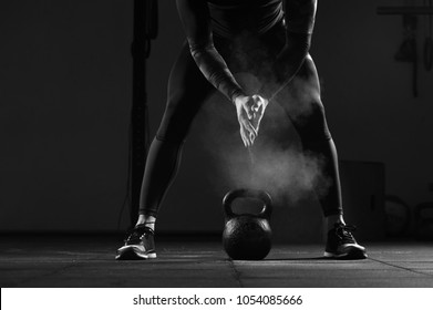 Close-up - Young muscular man working out in gym. Athletic male adult exercising with kettle bell. Fitness, sports concept.